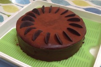 Dark Chocolate mousse cake with double cream & chocolate glaze, pure cocoa buttons & dusting